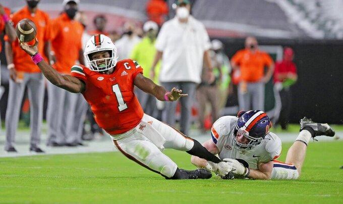 Miami quarterback D'Eriq King (1) is tackled by Virginia's  Zane Zandier (1) in the first half of an NCAA college football game in Miami Gardens, Fla., Saturday, Oct. 24, 2020. (Al Diaz/Miami Herald via AP)