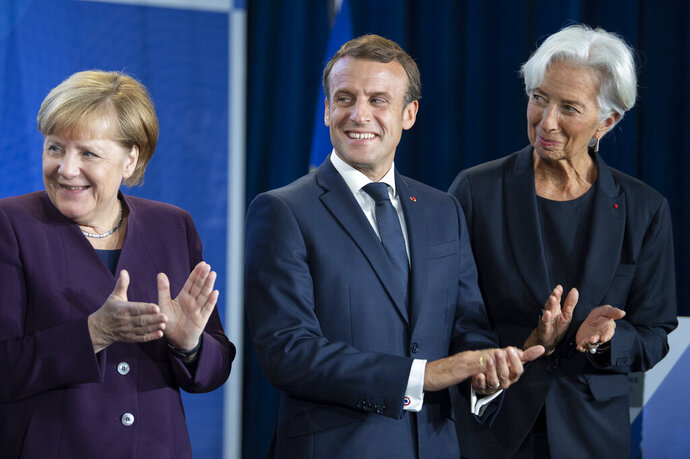 From right, new European Central Bank President Christine Lagarde, French President Emmanuel Macron and German Chancellor Angela Merkel applaud at a ceremony celebrating the change at the head of the ECB in Frankfurt, Germany, Monday, Oct. 28, 2019. Draghi leaves as head of the European Central Bank credited with having rescued the eurozone from disaster with a well-timed phrase and bold action to back up his words. (Boris Roessler/Pool Photo via AP)