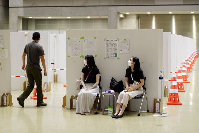 Workers, center, help direct a man into a booth for a coronavirus infection test at the Main Press Center for the 2020 Summer Olympics, Thursday, July 29, 2021, in Tokyo, Japan. About 30,000 people from scores of nations are spitting into tiny plastic vials every day at the Olympics in a routine that's grown crucial in going ahead with the pandemic-era Games, according to organizers. (AP Photo/Hiro Komae)