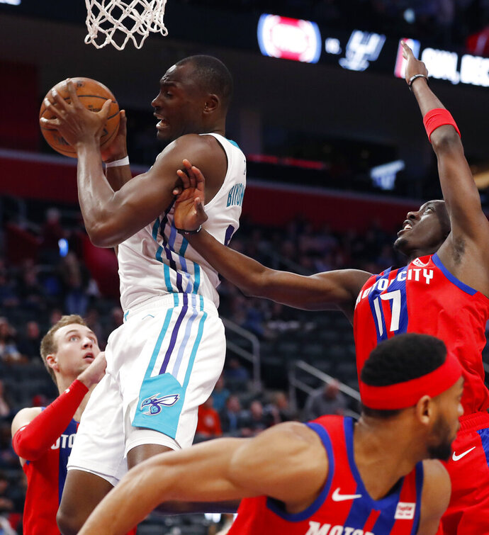 Charlotte Hornets center Bismack Biyombo, top left, grabs a rebound next to Detroit Pistons guard Tony Snell (17) during the second half of an NBA basketball game, Friday, Nov. 29, 2019, in Detroit. (AP Photo/Carlos Osorio)
