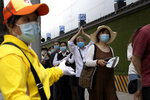 A resident makes a gesture as he lines up with other residents for COVID-19 test outside the Worker's Stadium in Beijing on Tuesday, June 30, 2020. Test sites have sprung up through the Chinese capital as test have become a daily normal after the latest outbreak of the coronavirus, (AP Photo/Ng Han Guan)