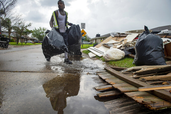 Travis Hutchinson splashes through a puddle of water as he and his IV Waste co-workers pick up trash and storm debris following Hurricane Ida in Kenner, La., Monday, Sept. 6, 2021. (Chris Granger/The Times-Picayune/The New Orleans Advocate via AP)