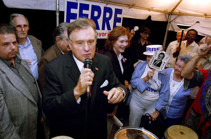 FILE- In This Oct. 26, 2001 file photo, Maurice Ferre, with microphone addresses supporters in the Little Havana district of Miami. Ferre was the Miami mayor from 1973-1985. Ferre died Thursday, Sept. 19, 2019. He was 84. (AP Photo/Tony Gutierrez, File)