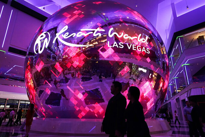 FILE - In this June 24, 2021, file photo, people walk by an illuminated sphere during the the opening night of the Resorts World Las Vegas hotel-casino in Las Vegas. Nevada casinos rode a robust economic rebound from coronavirus restrictions in June, taking in more than $1 billion in winnings for the fourth straight month and nearly reaching the all-time record set a month earlier, state regulators reported Thursday, July 29, 2021. (AP Photo/John Locher, File)