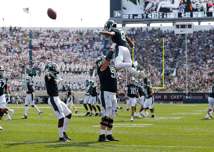 Michigan State receiver Jalen Nailor, top, offensive guard Matt Carrick (56) and receiver Jayden Reed, left, celebrate Nailor's touchdown reception against Youngstown State during the third quarter of an NCAA college football game, Saturday, Sept. 11, 2021, in East Lansing, Mich. Michigan State won 42-14. (AP Photo/Al Goldis)