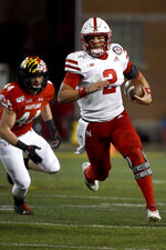 Nebraska quarterback Adrian Martinez (2) runs in front of Maryland linebacker Chance Campbell (44) during the second half of an NCAA college football game, Saturday, Nov. 23, 2019, in College Park, Md. (AP Photo/Will Newton)