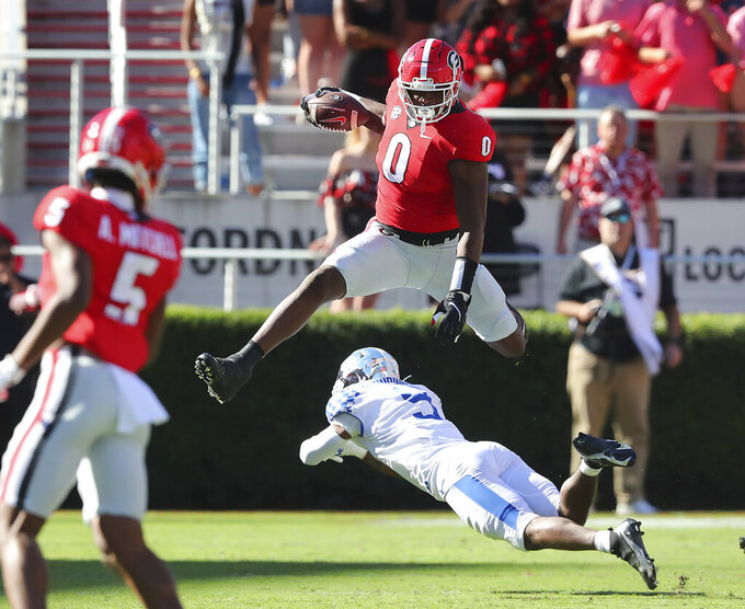 Georgia tight end Darnell Washington leaps over Kentucky defender DeAndre Square for a first down during the first quarter of an NCAA college football game against Kentucky, Saturday, Oct. 16, 2021, in Athens, Ga. (Curtis Compton/Atlanta Journal-Constitution via AP)