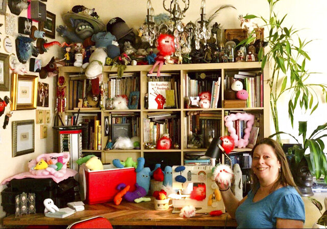 "This July 25, 2020 photo shows Amy Micallef posing with her craft creations at her home. While Broadway stages remain dark due to the pandemic, Broadway workers are concentrating on side hustles. Micallef, a Broadway seamstress who has worked in the wardrobe departments of ""Hamilton,"" ""Waitress"" and ""Frozen,"" makes gleeful representations of COVID-19 for sale, complete with a pair of eyes and faux fur. (Amy Micallef via AP)"