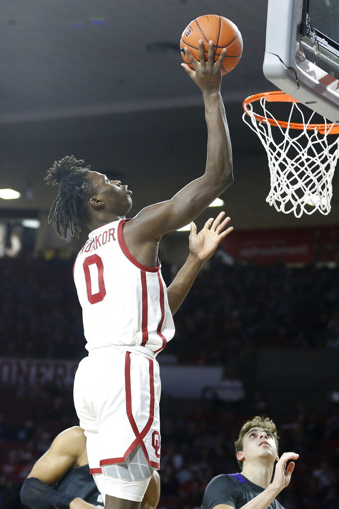 Oklahoma Sooners forward Victor Iwuakor (0) takes a shot against TCU's Francisco Farabello (3) and Jaedon Ledee (23) during the second half of an NCAA college basketball game in Norman, Okla., Saturday, Jan. 18, 2020. (AP Photo/Garett Fisbeck)