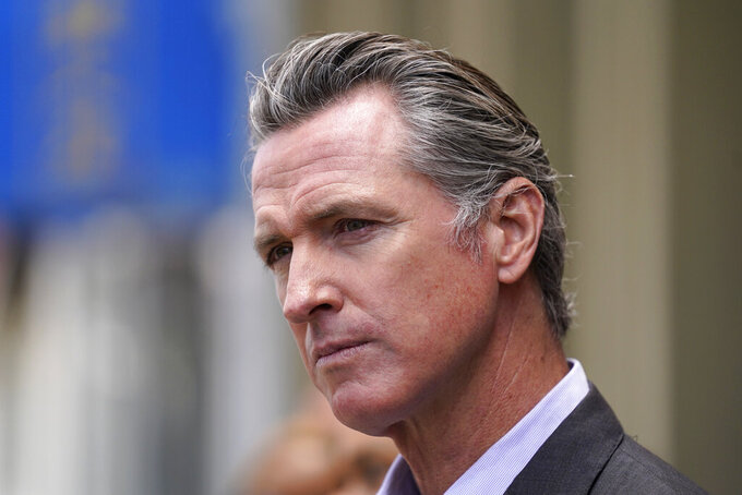 California Gov. Gavin Newsom listens to questions during a news conference outside a restaurant in San Francisco, on Thursday, June 3, 2021. Business and agricultural groups are renewing their criticism of new rules adopted by Gov. Newsom's workplace regulators. But there is little chance they can quickly change them unless Newsom steps in, which he seemed disinclined to do Friday.(AP Photo/Eric Risberg)