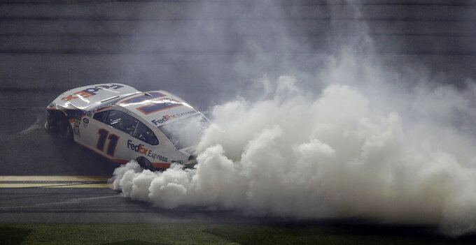 Denny Hamlin burns his tires after winning a NASCAR Daytona 500 auto race Sunday, Feb. 17, 2019, at Daytona International Speedway in Daytona Beach, Fla. (AP Photo/Chris O'Meara)