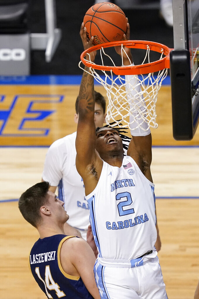 North Carolina guard Caleb Love (2) goes up for a basket in front of Notre Dame forward Nate Laszewski (14) during the first half of an NCAA college basketball game in the second round of the Atlantic Coast Conference tournament in Greensboro, N.C., Wednesday, March 10, 2021. (AP Photo/Gerry Broome)