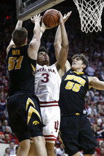 Indiana forward Justin Smith (3) shoots between Iowa defenders Nicholas Baer (51) and Luka Garza (55) during the second half of an NCAA college basketball game in Bloomington, Ind., Thursday, Feb. 7, 2019. Iowa won 77-72. (AP Photo/AJ Mast)