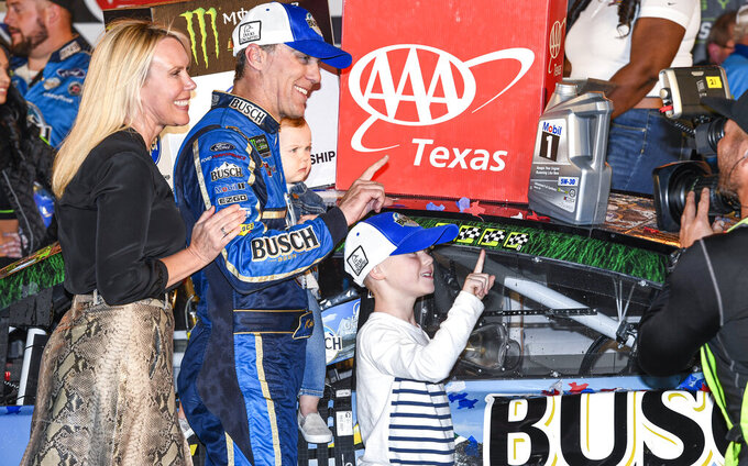 Kevin Harvick and his family celebrate in Victory Lane after winning a NASCAR Cup Series auto race at Texas Motor Speedway, Sunday, Nov. 3, 2019, in Fort Worth, Texas. (AP Photo/Larry Papke)