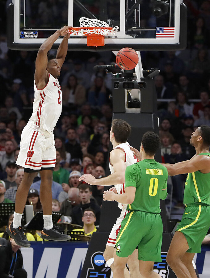 Wisconsin guard Khalil Iverson, left, dunks against Oregon during the first half a first-round game in the NCAA men's college basketball tournament Friday, March 22, 2019, in San Jose, Calif. (AP Photo/Chris Carlson)