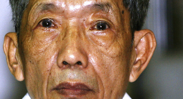 FILE - In this March 30, 2009, file photo, former Khmer Rouge prison commander Kaing Guek Eav, also know as Duch looks on during the first full day of a U.N.-backed tribunal in Phnom Penh, Cambodia. The Khmer Rouge's chief jailer, who admitted overseeing the torture and killings of as many as 16,000 Cambodians while running the regime's most notorious prison, died at a hospital in Cambodia early Wednesday morning, Sept. 2, 2020. Kaing Guek Eav, known as Duch, was 77 and had been serving a life prison term for war crimes and crimes against humanity. (Mak Remissa/Pool Photo via AP, File)