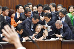 Japan's opposition parties' members try to stop Judicial Affairs Committee Chairman Shinichi Yokoyama, bottom center, from moving to hold a vote for a bill to revise an immigration control law, at upper house committee in Tokyo early Saturday, Dec. 8, 2018. Japan is preparing to officially open the door to foreign workers to do unskilled jobs and possibly eventually become citizens. (Yoshitaka Sugawara/Kyodo News via AP)
