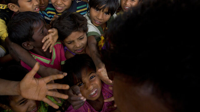 In this Wednesday, Jan. 17, 2018, file photo, Rohingya refugee children push each other to receive a packet of Khichdi, made from rice and lentils, at a food distribution centre in Balukhali refugee camp near Cox's Bazar, Bangladesh. United Nations agencies are warning that more than 350 million people in the Asia-Pacific are going hungry as the coronavirus pandemic destroys jobs and pushes food prices higher. (AP Photo/Manish Swarup, File)