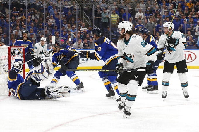 FILE - In this May 15, 2019, file photo, San Jose Sharks defenseman Erik Karlsson (65), of Sweden, scores the winning goal past St. Louis Blues goaltender Jordan Binnington (50) during overtime in Game 3 of the NHL hockey Stanley Cup Western Conference final series in St. Louis. A major officiating gaffe occurred in the Stanley Cup playoffs when San Jose's Karlsson scored a goal set up by a hand pass. While hockey officials have the toughest job _ they must be able to skate like the players _ they do not get a pass for their mistakes, either. (AP Photo/Jeff Roberson, File)