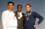FILE - In this Sept. 6, 1960, file photo, the top three finishers in the decathlon of the 1960 Rome Summer Olympics stand on the podium while wearing their medals at Olympic Stadium in Rome. Rafer Johnson, center, won the gold; Taiwan's Yang Chuan, left, the silver; and Russia's Vasili Kuznetsov the bronze. Rafer Johnson, who won the decathlon at the 1960 Rome Olympics and helped subdue Robert F. Kennedy's assassin in 1968, died Wednesday, Dec. 2, 2020. He was 86. He died at his home in the Sherman Oaks section of Los Angeles, according to family friend Michael Roth.(AP Photo/File)