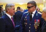 In this photo taken on Thursday, Feb. 14, 2019, Vladimir Vshivtsev, a veteran of the Soviet war in Afghanistan, right, and Gen. Col. Boris Gromov, former Commander of the 40th Army in Afghanistan, greet each other during a meeting at the upper chamber of Russian parliament in Moscow, Russia. Vshivtsev, who was wounded in action and lost his eye-sight, became a leading activist in the Russian Society for the Blind and served a stint in the Russian parliament. (AP Photo/Alexander Zemlianichenko)