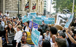 Alexandria Ocasio-Cortez, far left, the surprise winner in the congressional race who unseated 20-year incumbent Joe Crowley in New York's Congressional District 14, raises the hand of Zephyr Teachout, endorsing her candidacy for Attorney General during a press conference next to the Wall Street Bull statue, Thursday, July 12, 2018, in New York. (AP Photo/Bebeto Matthews)