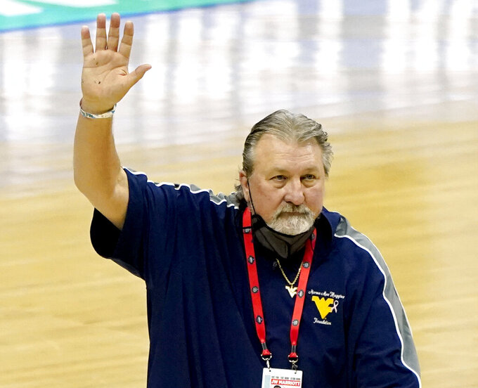 FILE - In this March 20, 2021, file photo, West Virginia head coach Bob Huggins waves to the crowd as he leaves the court following a win over Morehead State in a college basketball game in the first round of the NCAA tournament at Lucas Oil Stadium in Indianapolis. Huggins has agreed to a two-year contract extension that includes the option for him to step aside or continue coaching after the 2023-24 season. (AP Photo/Mark Humphrey, File)