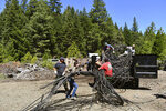 In this May 7, 2019, photo released by Cannabis Removal on Public Lands (CROP) Project, workers from Trinity County RCD/Watershed Center, along with Jackee Riccio, CROP Regional Field Director, center, prepare trash to be air lifted for disposal from a trespass grow complex where nearly 9,000 illegally cultivated cannabis plants where found in the Shasta-Trinity National Forest, in Calif. Authorities allege members of an international drug trafficking ring set up camp at the site months earlier. Along with the hundreds of pounds of harvested marijuana, they also found thousands of pounds of trash and more than three miles (4.8 kilometers) of plastic irrigation piping, according to the Trinity County Sheriff's Office. (Dane Curry/CROP via AP)