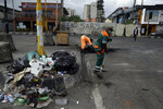 Volunteers sweep debris on the roads in Lagos Saturday, Oct. 24, 2020. Nigeria's president says 51 civilians have been killed in unrest following days of peaceful protests over police abuses, and he blames