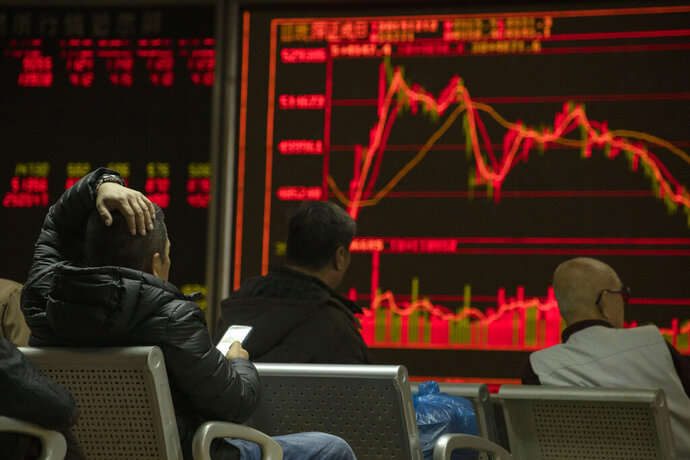 Investors monitors stock prices at a brokerage in Beijing on Thursday, Dec. 12, 2019. Asian shares are mixed after a wobbly day on Wall Street following the Federal Reserve announcement that it would leave interest rates unchanged. Japan's benchmark Nikkei 225, South Korea's Kospi and Hong Kong's Hang Seng rose in early Thursday trading. (AP Photo/Ng Han Guan)
