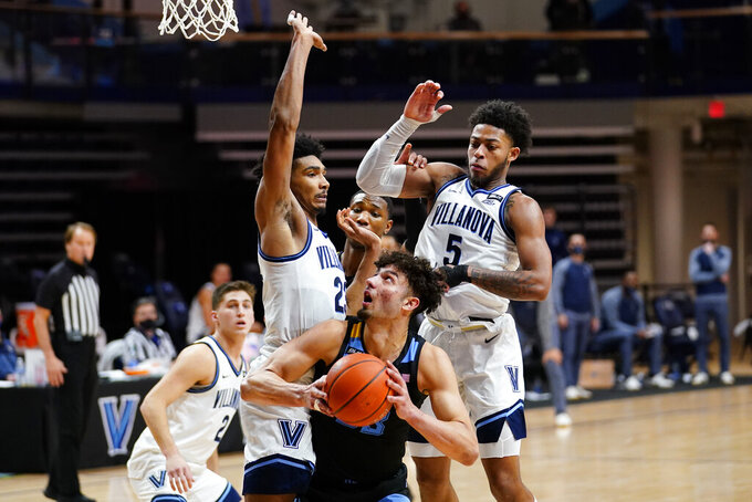 Marquette's Dawson Garcia, center, tries to get a shot past Villanova's Jermaine Samuels, left, and Justin Moore during the second half of an NCAA college basketball game, Wednesday, Feb. 10, 2021, in Villanova, Pa. (AP Photo/Matt Slocum)