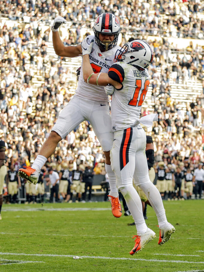 Oregon State wide receiver Trevon Bradford (8) celebrates a fourth-quarter touchdown with Timmy Hernandez (18) during an NCAA college football game against Colorado, Saturday, Oct. 27, 2018, in Boulder, Colo. (AP Photo/Jack Dempsey)