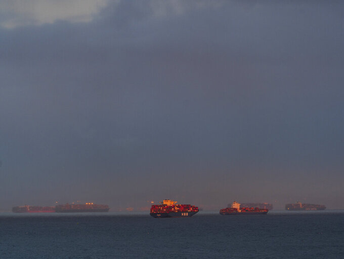 In this Wednesday, March 3, 2021 photo, a high number of container ships dot the coast of Long Beach at sunset waiting to dock at the Ports of Los Angeles and Long Beach off the California Coast. A trade bottleneck born of the COVID-19 outbreak has U.S. businesses waiting for shipments from Asia _ while off the coast of California, dozens of container ships have been anchored, unable to unload their cargo.   ( AP Photo/Damian Dovarganes)