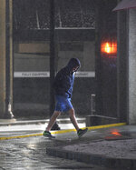 In this Sunday, Dec. 1, 2019 photo, a man heads into a CVS Pharmacy on Front Street as it snows in Worcester, Mass. A wintry storm that made Thanksgiving travel miserable across much of the country gripped the East with a messy mixture of rain, snow, sleet and wind.  (Christine Peterson/Worcester Telegram & Gazette via AP)