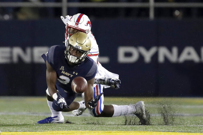 Navy wide receiver Mychal Cooper, front, dives to make a catch on a pass from quarterback Malcolm Perry as SMU defensive back Brandon Stephens, back, defends him during the first half of an NCAA college football game, Saturday, Nov. 23, 2019, in Annapolis, Md. (AP Photo/Julio Cortez)