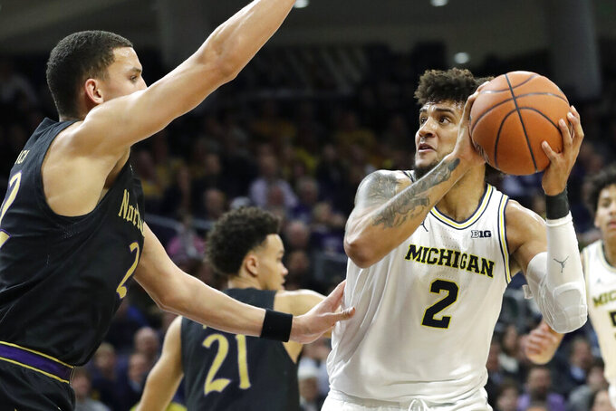 Michigan forward Isaiah Livers, right, looks to the basket against Northwestern forward Pete Nance during the first half of an NCAA college basketball game in Evanston, Ill., Wednesday, Feb. 12, 2020. (AP Photo/Nam Y. Huh)