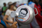 A demonstrator bangs on a pot that has a cartoon drawing of Governor Ricardo Rossello and text the reads in Spanish
