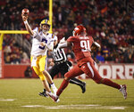 LSU quarterback Joe Burrow throws a pass over Arkansas defender Michael Taylor II during the first half of an NCAA college football game, Saturday, Nov. 10, 2018, in Fayetteville, Ark. (AP Photo/Michael Woods)