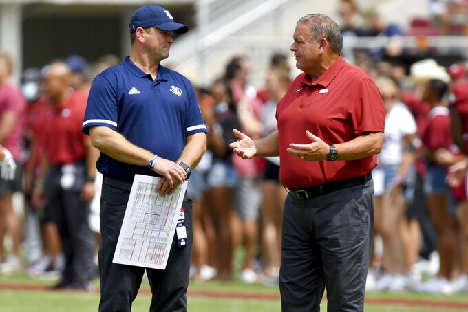 Rice coach Mike Bloomgren, left, and Arkansas coach Sam Pittman talk before the start of their NCAA college football game Saturday, Sept. 4, 2021, in Fayetteville, Ark. (AP Photo/Michael Woods)