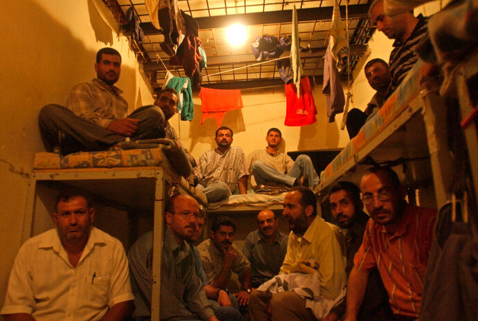 FILE - This August 3, 2005 file photo, Lebanese ex-inmates of the notorious Khiam prison sit in their former cells where they displayed their belongings during a sit-in at the Khiam prison, in southern Lebanon. Lebanon General Security Directorate says it has referred a Lebanese-American to prosecutors after he confessed that he worked for Israel. Amer Fakhoury was detained days after returning to Lebanon earlier Sept. 2019 for being a top warden at the Khiam Prison that was run by the Israeli-backed South Lebanon Army militia until Israel ended an 18-year occupation in 2000. (AP Photo/Mohammad Zaatari, File)
