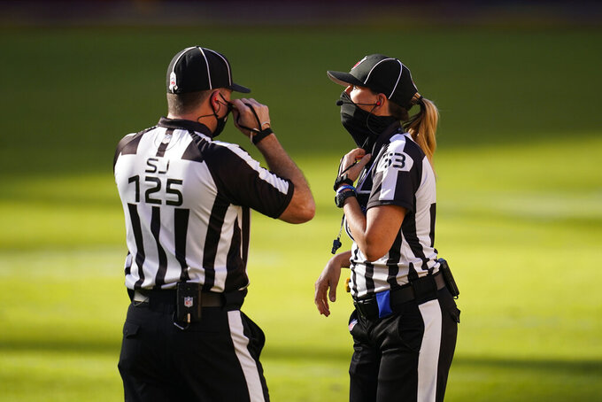 Side Judge Chad Hill (125) and Down Judge Sarah Thomas (53) confer with one another during the first half of an NFL football game between the New York Giants and Washington Football Team, Sunday, Nov. 8, 2020, in Landover, Md. (AP Photo/Patrick Semansky)