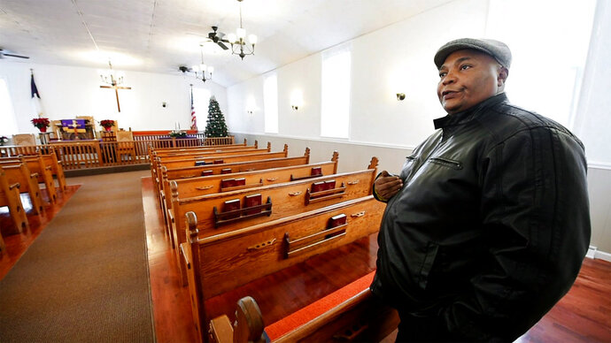 In this undated photo, The Rev. Marlon Carter stands in the newly refurbished Fawn AME Zion Church, in New Park, Pa. Carter said it touches his heart every time he enters the church when he thinks of all the work the congregation endured and the history of an African American church that formed before the Civil War. (Paul Kuehnel/York Daily Record via AP)