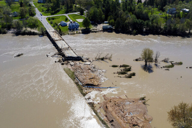 In this Wednesday, May 20, 2020, photo, people survey the flood damage to the Curtis Road Bridge in Edenville, Mich., over the Tittabawassee River. The bridge sits just south of Wixom Lake where the dams failed. (Neil Blake/The Grand Rapids Press via AP)