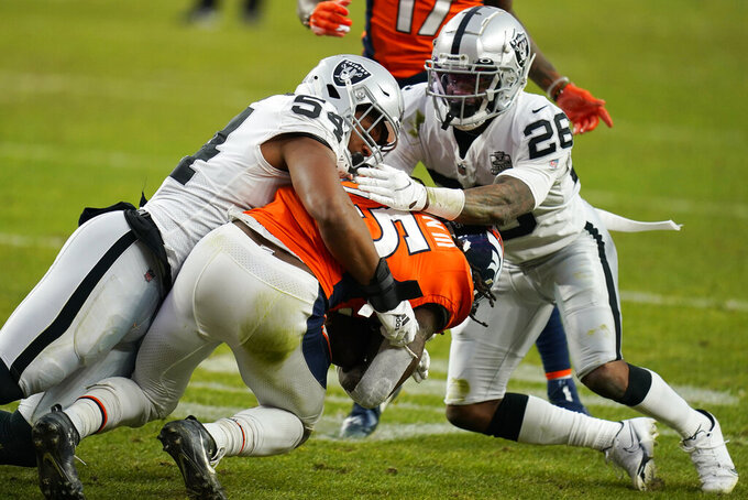 Las Vegas Raiders middle linebacker Raekwon McMillan (54) and cornerback Nevin Lawson (26) tackle Denver Broncos running back Melvin Gordon (25) during the first half of an NFL football game, Sunday, Jan. 3, 2021, in Denver. (AP Photo/Jack Dempsey)