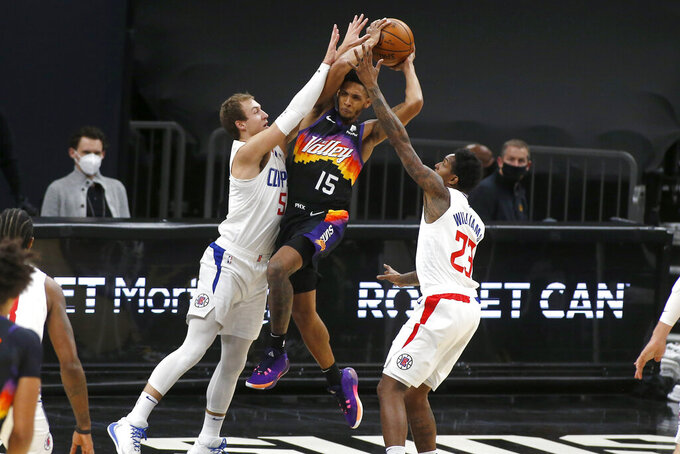 Phoenix Suns guard Cameron Payne (15) drives to the basket between the defense of Los Angeles Clippers guards Luke Kennard (5) and Lou Williams (23) during the first half of an NBA basketball game Sunday, Jan. 3, 2021, in Phoenix. (AP Photo/Ralph Freso)
