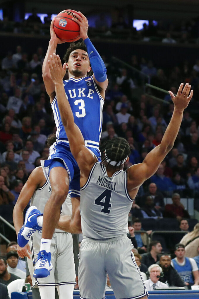 Duke guard Tre Jones (3) leaps over Georgetown guard Jagan Mosely (4) for a shot during the first half of an NCAA college basketball game in the 2K Empire Classic, Friday, Nov. 22, 2019 in New York. (AP Photo/Kathy Willens)
