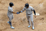 New York Yankees' Brett Gardner, left, celebrates with Gio Urshela after scoring on a two-run single by Austin Romine during the third inning of a baseball game against the Chicago White Sox in Chicago, Sunday, June 16, 2019. (AP Photo/Nam Y. Huh)