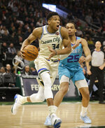 Milwaukee Bucks' Giannis Antetokounmpo drives past Charlotte Hornets' P.J. Washington during the second half of an NBA basketball game Saturday, Nov. 30, 2019, in Milwaukee. (AP Photo/Jeffrey Phelps)