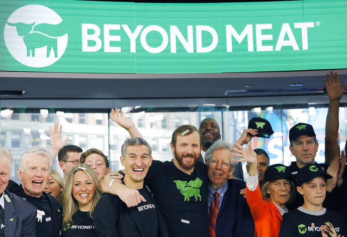 FILE - In this May 2, 2019, file photo Ethan Brown, center, CEO of Beyond Meat, attends the Opening Bell ceremony with guests to celebrate the company's IPO at Nasdaq in New York. After another two-day surge, shares in Beyond Meat are now selling for more than six times their $25 IPO price early last month. But some are beginning to wonder if they're finally priced beyond their actual value. JPMorgan on Tuesday, June 11 downgraded the stock from buy to neutral. (AP Photo/Mark Lennihan, File)
