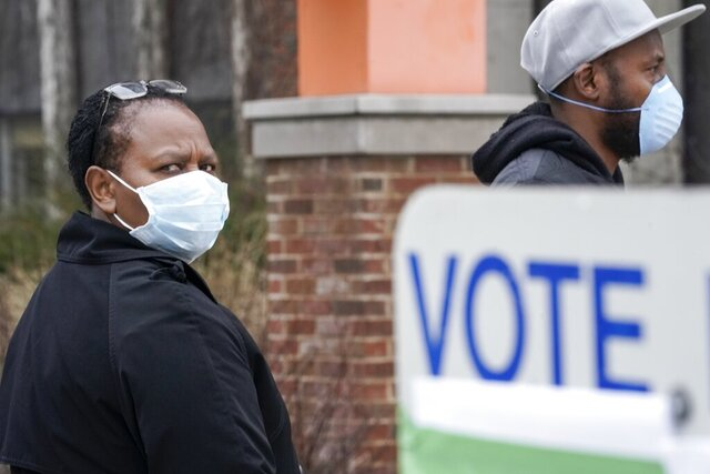 Voters masked against coronavirus line up at Riverside High School for Wisconsin's primary election Tuesday April 7, 2020, in Milwaukee. The new coronavirus causes mild or moderate symptoms for most people, but for some, especially older adults and people with existing health problems, it can cause more severe illness or death. (AP Photo/Morry Gash)